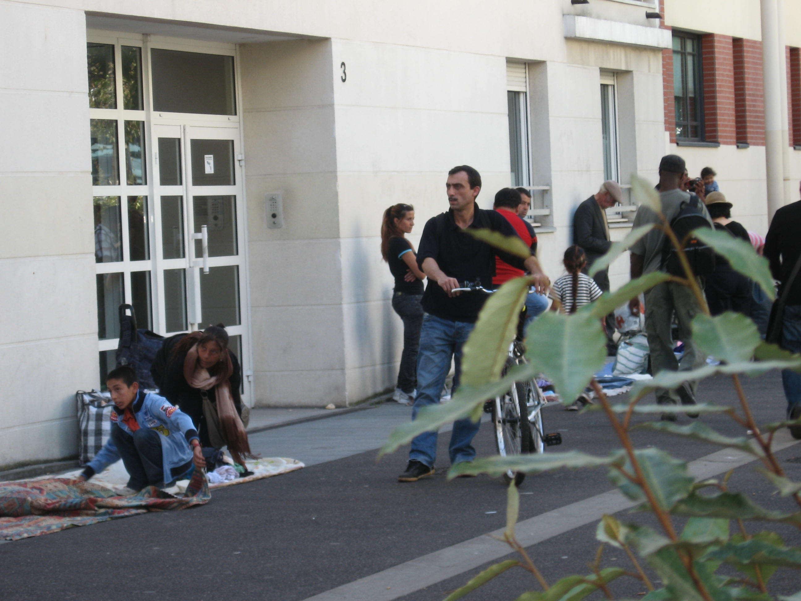 vendeurs à la sauvette devant une porte d'entrée d'immeuble
